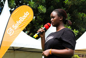 Joy, restless development volunteer from the Girls Advocacy Alliance giving a speech to the police, government and male motorbike taxi drivers about ending sexual harassment and violence against women